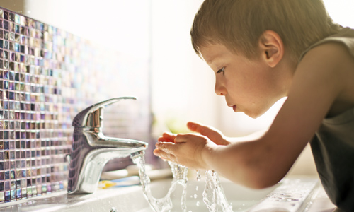 Photo of boy drinking from sink